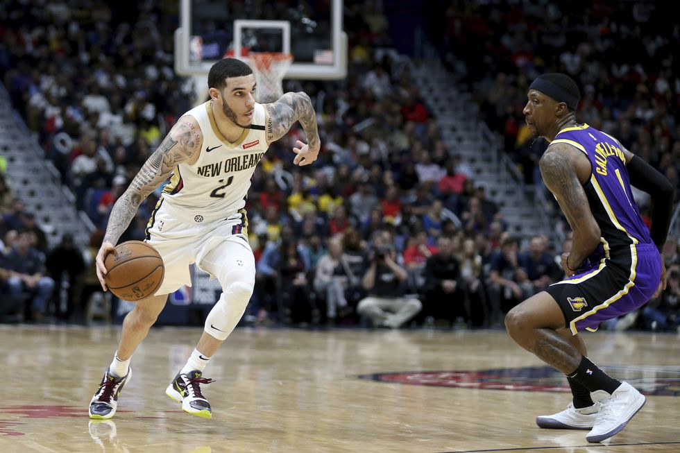 New Orleans Pelicans guard Lonzo Ball (2) dribbles past Los Angeles Lakers guard Kentavious Caldwell-Pope (1) in the second half of an NBA basketball game in New Orleans, Sunday, March 1, 2020. (AP Photo/Rusty Costanza)