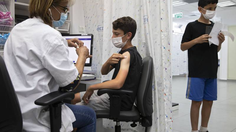 FILE - In this June 6, 2021 file photo, a youth receives a Pfizer-BioNTech COVID-19 vaccine in...