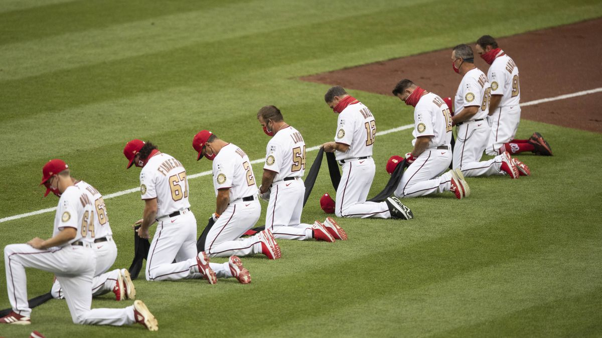 Members of Washington Nationals kneel and hold a piece of black fabric before an opening day...