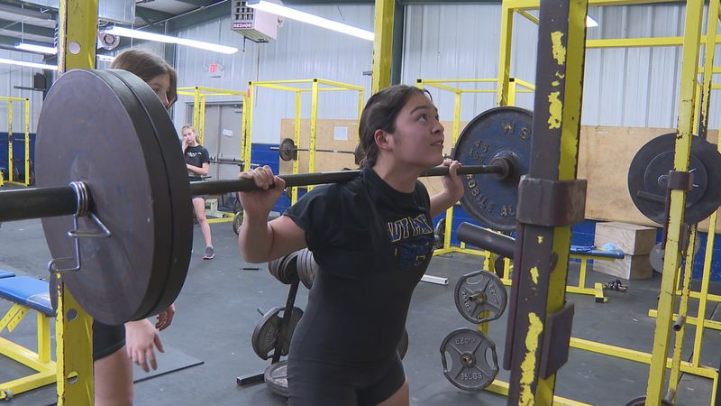 Quitman's Kristie Graves prepares to squat while her teammate stands nearby to spot her