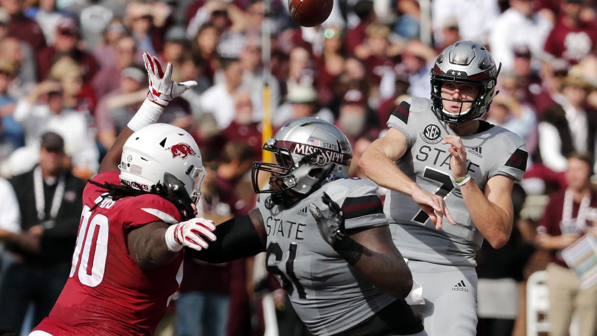 Mississippi State quarterback Nick Fitzgerald (7) passes against an on rushing Arkansas...