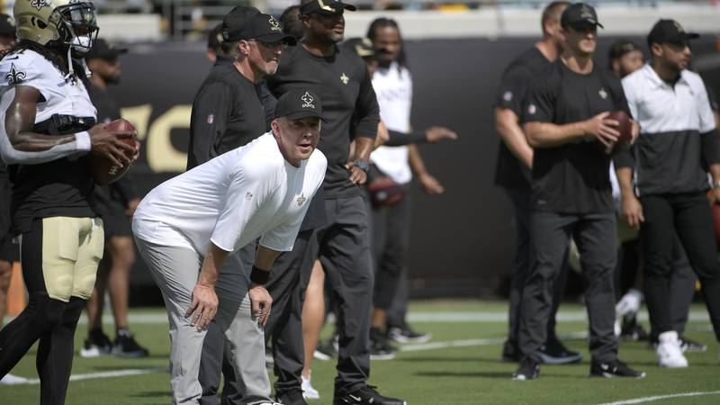 New Orleans Saints head coach Sean Payton, second from left, watches players warm up before an...
