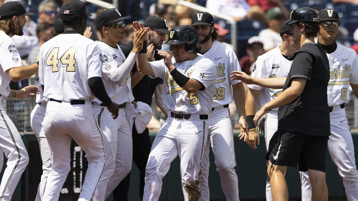 Vanderbilt's CJ Rodriguez (5) celebrates with teammates after scoring off a wild pitch from...