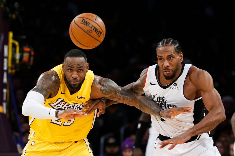 Los Angeles Lakers' LeBron James (23) and Los Angeles Clippers' Kawhi Leonard (2) chase the ball during an NBA basketball game between Los Angeles Lakers and Los Angeles Clippers, Wednesday, Dec. 25, 2019, in Los Angeles. The Clippers won 111-106. (AP Photo/Ringo H.W. Chiu)