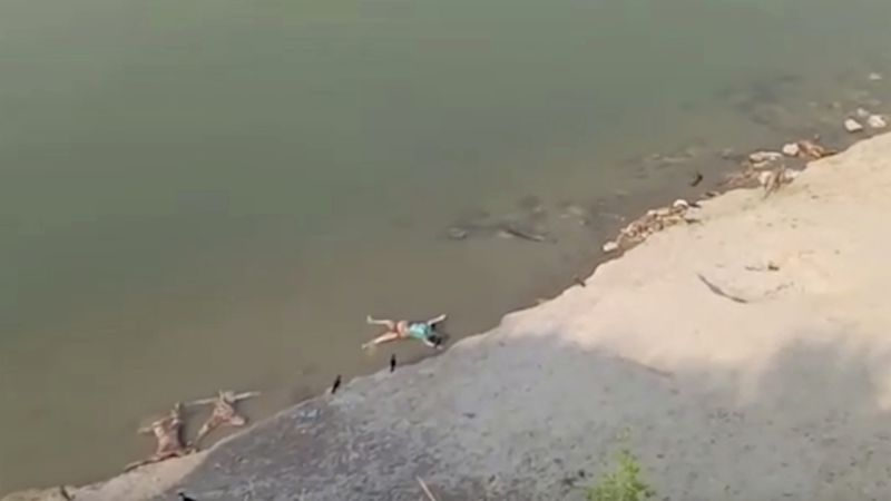 This frame grab from video provided by KK Productions shows bodies lying along the river in...