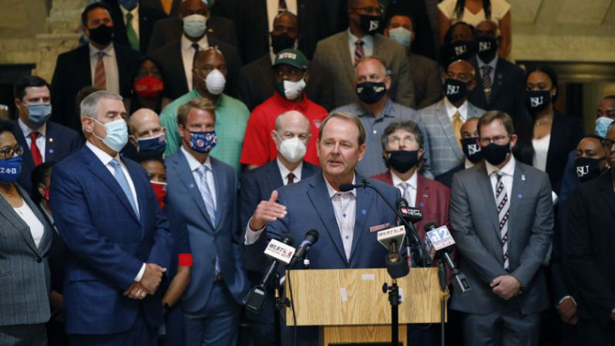 Mississippi basketball coach, Kermit Davis, center, joins other athletic staff from the state's public universities calling for a change in the Mississippi state flag, during a joint news conference at the Capitol in Jackson, Mississippi, on Thursday. Several head coaches met with both Lt. Gov. Delbert Hosemann and Speaker Philip Gunn in addition to their lawmakers, to lobby for the change by their respective bodies.