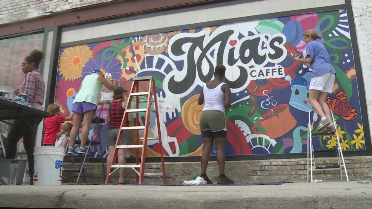 Volunteers work to finish mural at Mia's Caffe.
