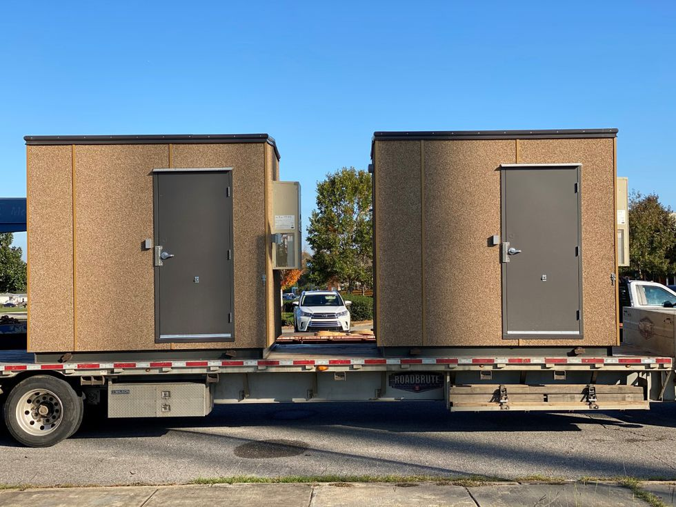 Storage buildings that will house fixed wireless broadband equipment are unloaded and affixed...