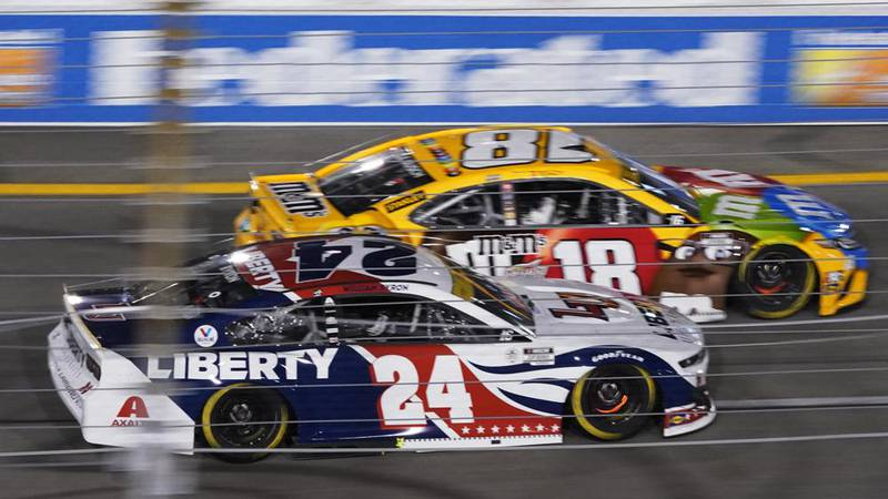 William Byron (24) and Kyle Busch (18) race into turn one during the NASCAR Cup series auto...