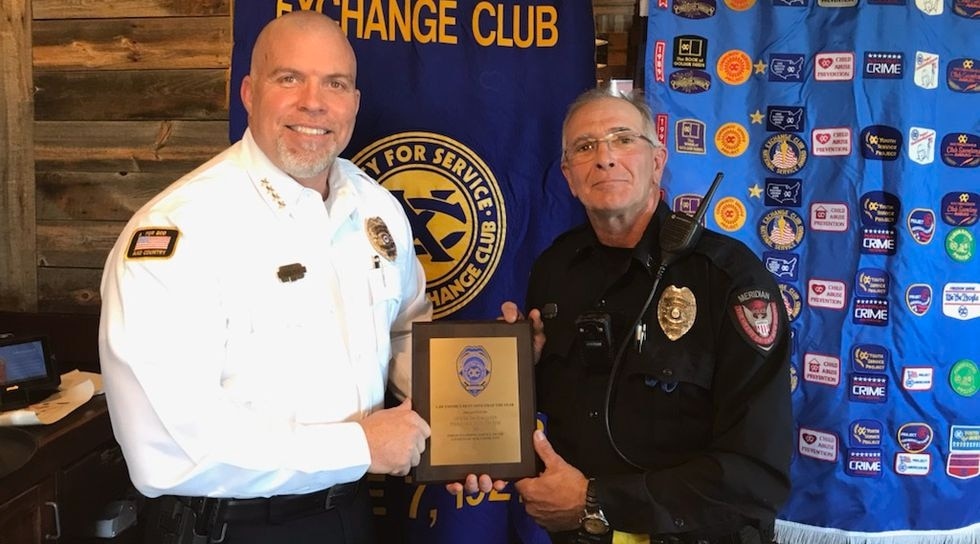 Police Chief Chris Read presents the Police Officer of the Year Award to officer David McQueen.