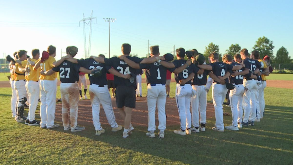 """Players huddle together following the conclusion of opening day of the """"Honor the Game"""" Collegiate Wood Bat League"""