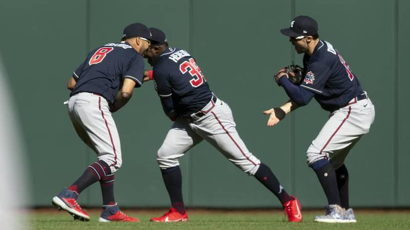 Atlanta Braves outfielders Eddie Rosario (8), Guillermo Heredia (38) and Adam Duvall celebrate...