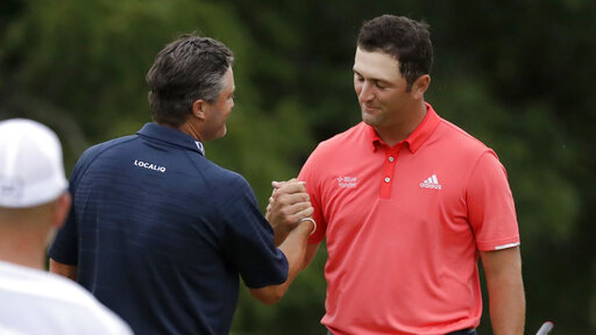Jon Rahm, of Spain, right, is congratulated by Ryan Palmer after winning the Memorial golf tournament, Sunday, July 19, 2020, in Dublin, Ohio. (AP Photo/Darron Cummings)