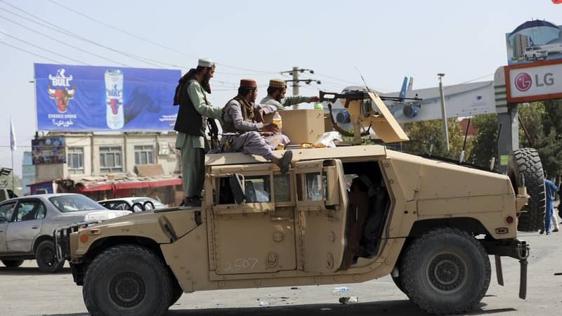 Taliban fighters stand guard in front of the Hamid Karzai International Airport, in Kabul,...