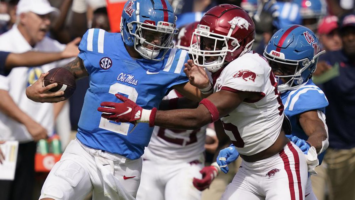 Mississippi quarterback Matt Corral, left, pushes off an Arkansas defender during the second...