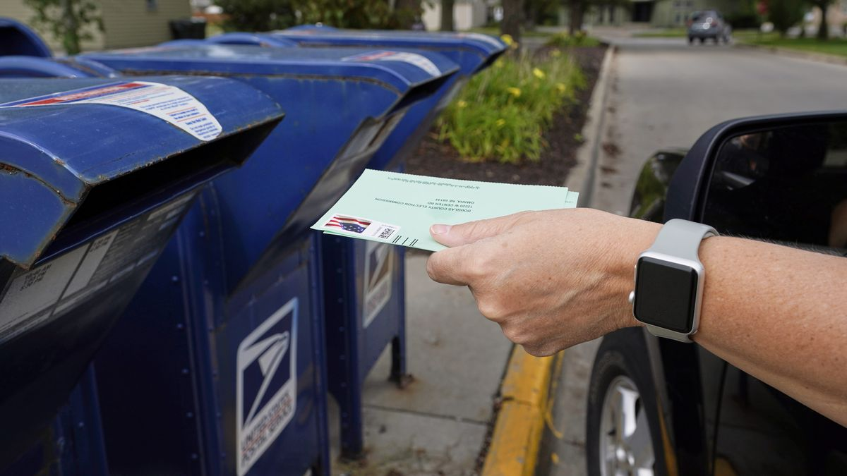 FILE - In this Tuesday, Aug. 18, 2020 file photo, a person drops applications for mail-in-ballots into a mailbox in Omaha, Neb.