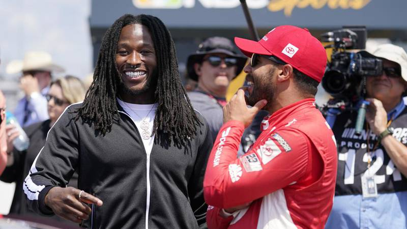 Alvin Kamara, left, running back with the NFL football New Orleans Saints, talks with driver...
