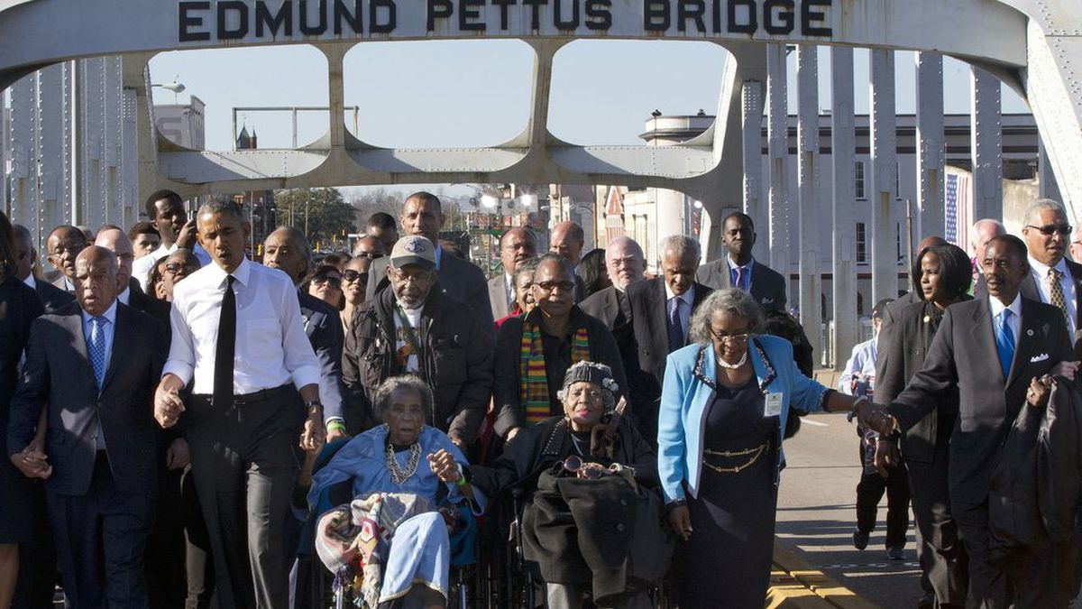 """In this March 7, 2015, file photo, singing """"We Shall Overcome,"""" President Barack Obama, third from left, walks holding hands with Amelia Boynton, who was beaten during """"Bloody Sunday,"""" as they and the first family and others including Rep. John Lewis, D-Ga, left of Obama, walk across the Edmund Pettus Bridge in Selma, Ala., for the 50th anniversary of """"Bloody Sunday,"""" a landmark event of the civil rights movement. Some residents in the landmark civil rights city of Selma, Ala., are among the critics of a bid to rename the historic bridge where voting rights marchers were beaten in 1965. (Source: AP Photo/Jacquelyn Martin, File)"""