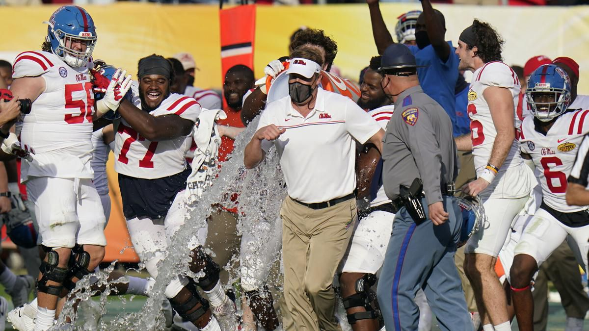 Mississippi head coach Lane Kiffin, center, runs to avoid getting doused with water by his team...