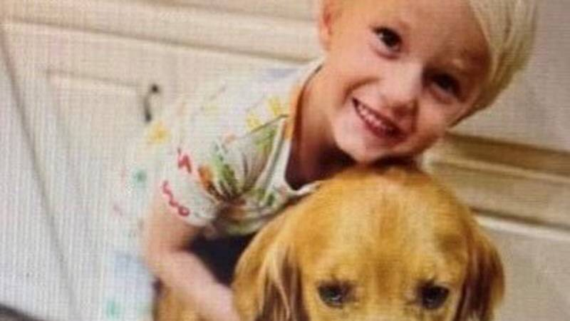 Henton Dean, 5-years-old, with one of the golden retrievers.