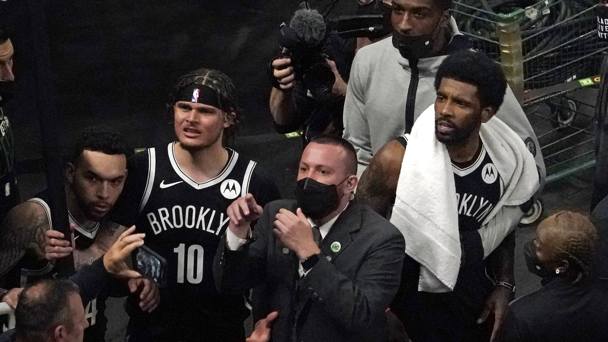 A security guard points as the Brooklyn Nets' Kyrie Irving, right with towel, and teammates...