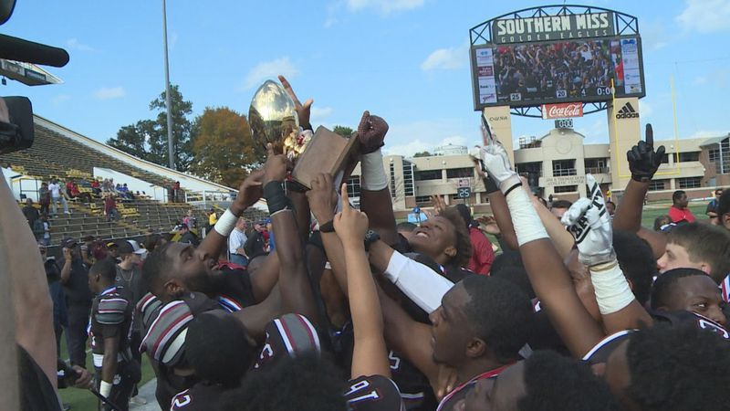 Louisville High School football hoisting the state championship trophy after beating...