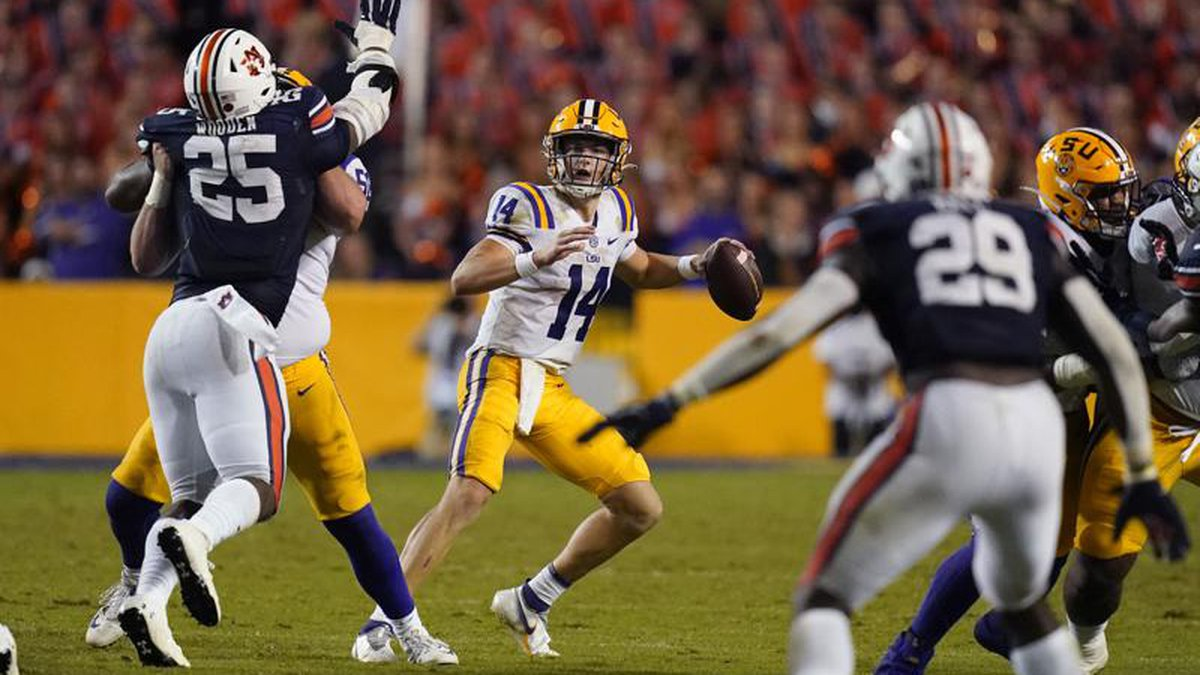 LSU quarterback Max Johnson (14) looks to pass under pressure from Auburn defensive end Colby...