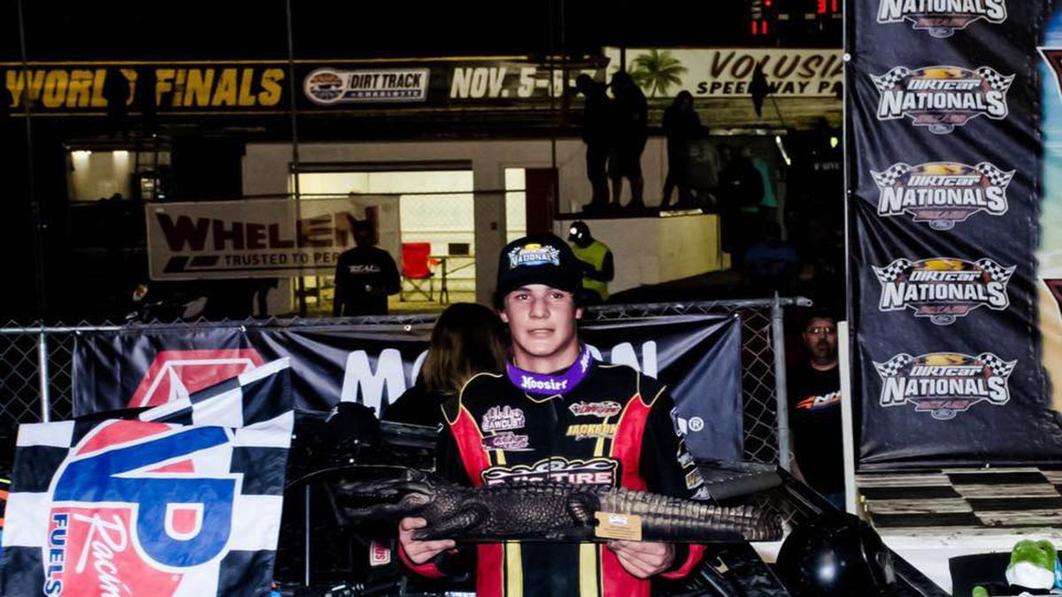 Spencer Hughes poses with his alligator trophy and check after winning a dirt track race in Feb.