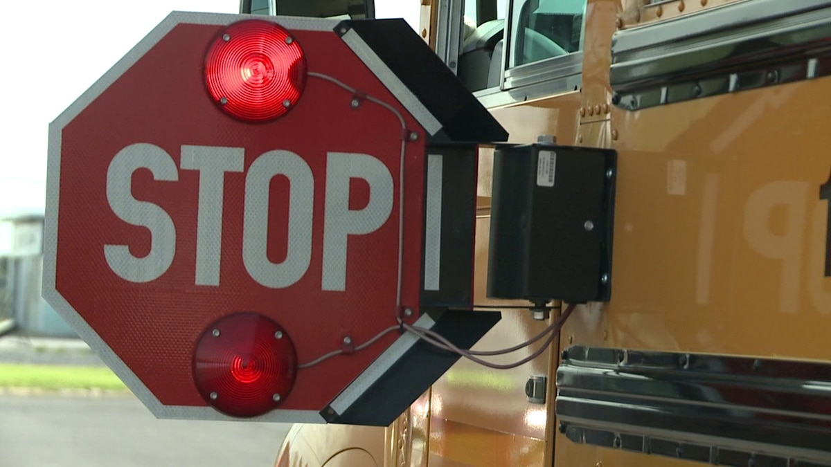 The law requires traffic to stop in both directions when the school bus stop sign is extended.