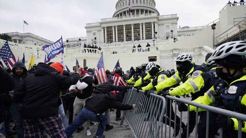 FILE - In this Jan. 6, 2021 file photo, Trump supporters try to break through a police barrier...