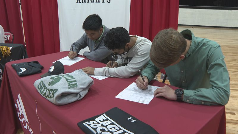 Left to right: Sam Balderas, Ivan Betancourt and Landon Williams all sign National Letters of...