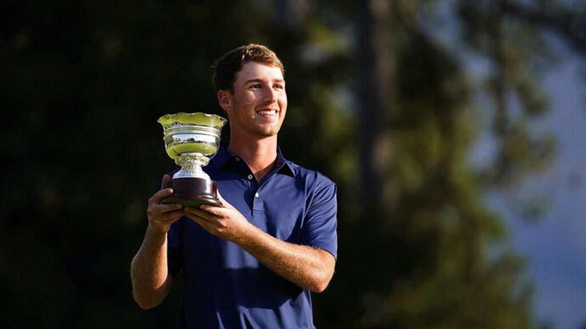 Andy Ogletree poses with his low amateur trophy following the Masters golf tournament Sunday,...