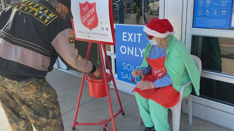 Bell ringer Elsie Dickerson watches, as a resident gives to the Salvation Army.