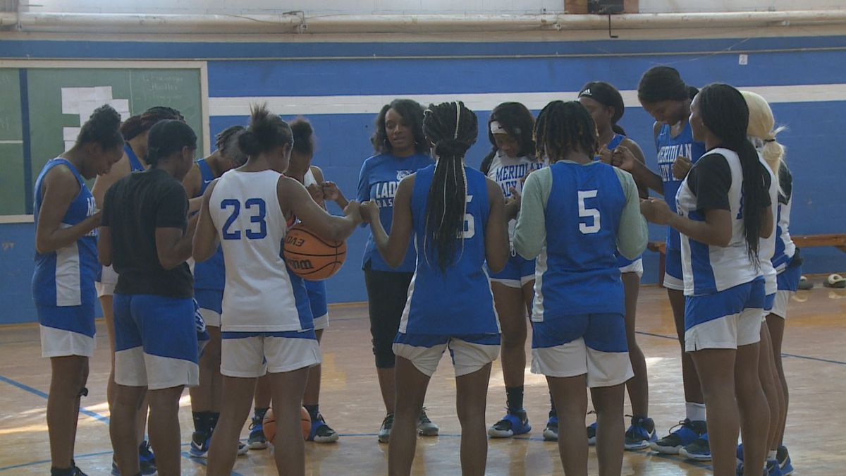 The Meridian girl's basketball team huddles together before practice