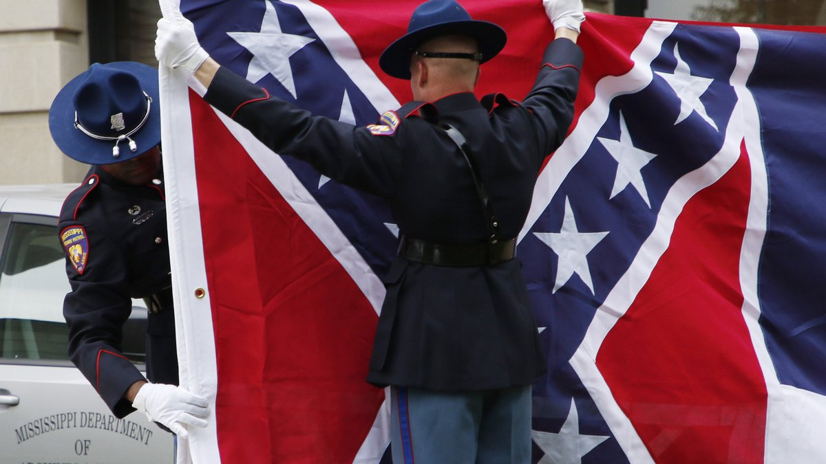 A Mississippi Highway Safety Patrol honor guard folds the retired Mississippi state flag after...