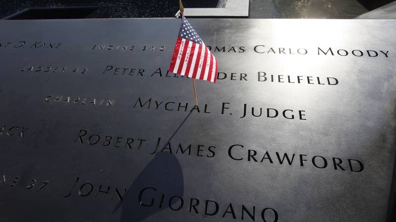 In this Monday, Sept. 12, 2011, file photo, a U.S. flag is stuck into the etched name of Father...
