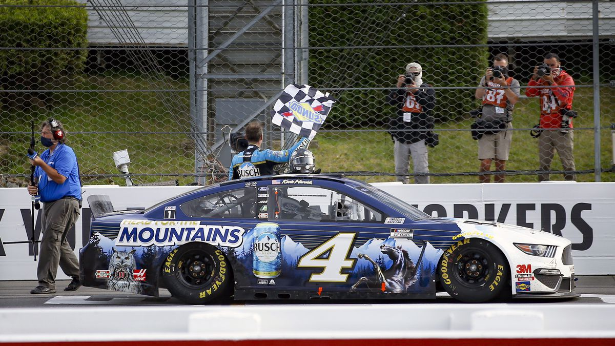 Kevin Harvick waves a checker flag for photographers after winning the NASCAR Cup Series auto...