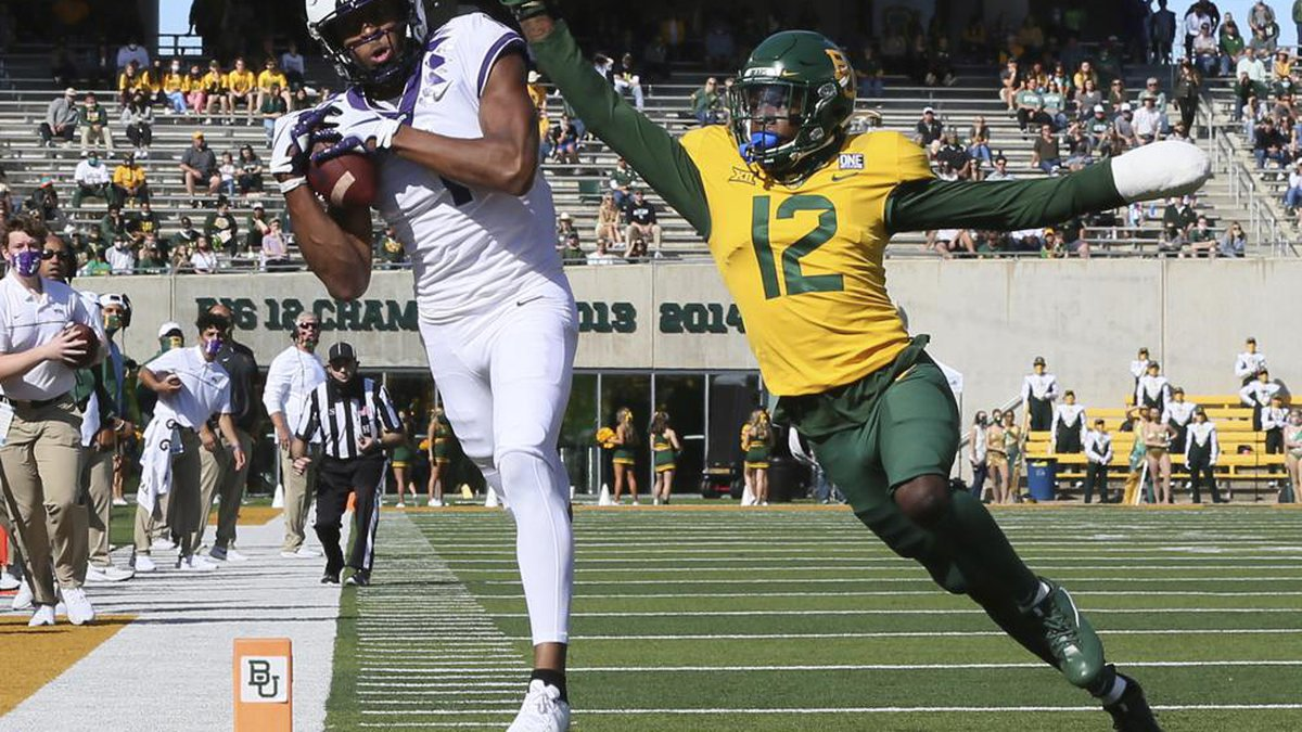 In this Oct. 31, 2020, file photo, TCU wide receiver Quentin Johnston, left, pulls in a pass...